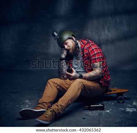 Tattooed bearded hipster skateboarder drinking beer.