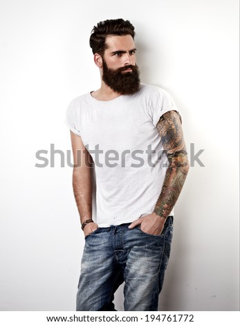 Tattooed bearded man wearing white blank t-shirt - stock photo