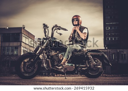 Tattooed biker and his bobber style motorcycle on a city streets  - stock photo