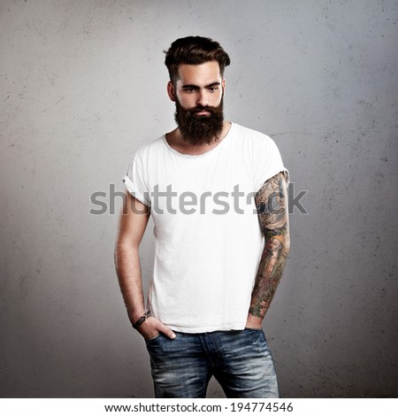 Tattooed brutal man wearing white blank t-shirt - stock photo