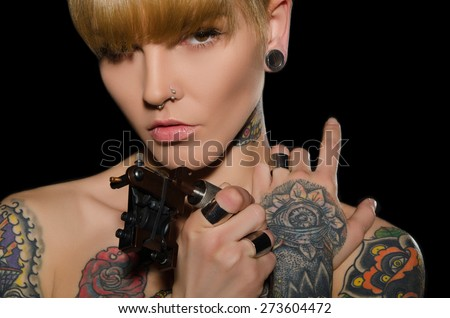 tattooed charming woman with tattoo machine, dark background