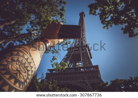 Tattooed hand with smartphone over background with eiffel tower. - stock photo