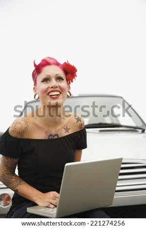 Tattooed Hispanic woman typing on laptop - stock photo
