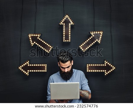 Tattooed man working with laptop and making decision - stock photo