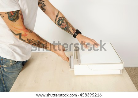 Tattooed unrecognizable man closes paper tray of home printer scanner multi device, isolated on white
