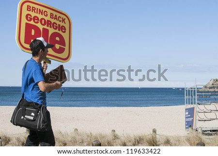 TAURANGA, NEW ZEALAND - NOVEMBER 4: A yung man carries the placard for a cause he is passionate about in Tauranga, New Zealand, November 4, 2012. Obtaining petition signatures is a common activity.