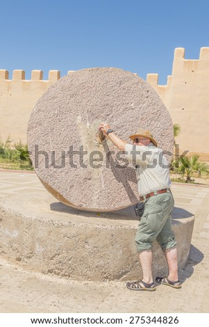 Taurodant, Morocco - tourists pose with old quern in front of historic ramparts - stock photo