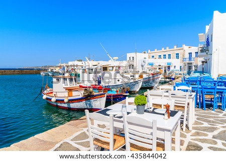 Taverna tables and typical Greek fishing boats in Naoussa port, Paros island, Cyclades, Greece - stock photo