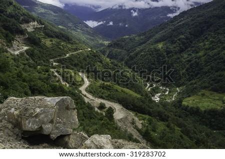 Tawang, Arunachal Pradesh, India. The main highway under construction and maintenance through the Himalyas connecting Assam with Tawang  as seen near Dirang, Arunachal Pradesh, India. - stock photo