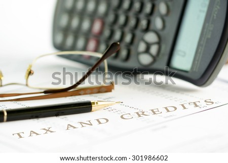 Tax and credits concept image of a pen, calculator and reading glasses on financial documents. - stock photo