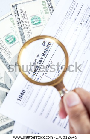 Tax audit concept with a magnifying glasses, tax form, and money - stock photo