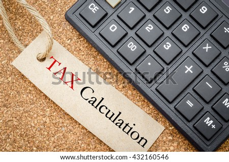 Tax calculation on recycle tag with calculator on wooden desk. Business concept. - stock photo
