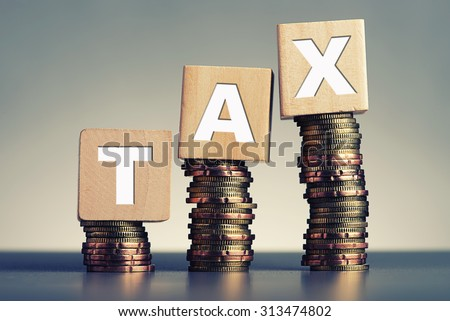 Tax Concept with wooden block on stacked coins - stock photo