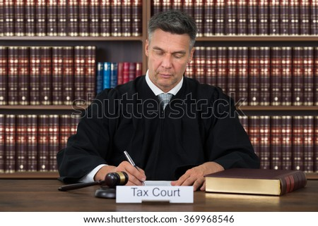 Tax court nameplate on table with judge writing on paper against bookshelf in courtroom - stock photo