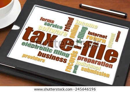 tax electronic filing concept - a word cloud on a digital tablet with a cup of tea - stock photo