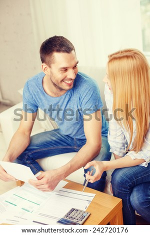 tax, finances, family, home and happiness concept - smiling couple with papers and calculator at home - stock photo