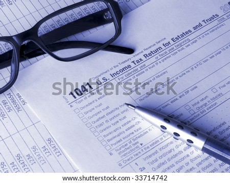 Tax form 1041 pen and glasses. Toned blue. Shallow DOF. - stock photo