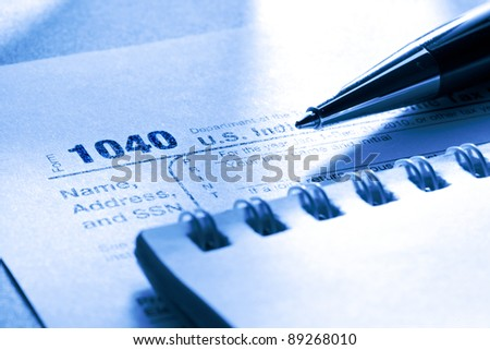 Tax form, pen and notepad - stock photo