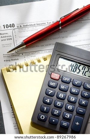 Tax form, red pen, notepad and calculator - stock photo