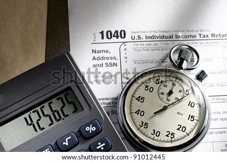 Tax form, stopwatch and calculator - stock photo