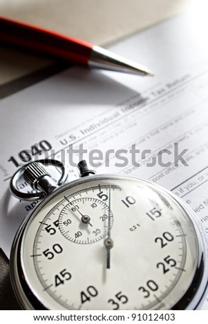 Tax form, stopwatch and pen - stock photo