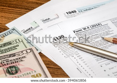 tax form w4, 1040, 1120 with pen and us dollar
