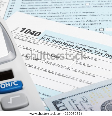 Tax Form 1040 with calculator and 100 US dollar bills - stock photo
