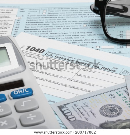 Tax Form 1040 with calculator, dollars and glasses - 1 to 1 ratio - stock photo