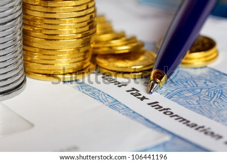 Tax form with coins and pen - stock photo