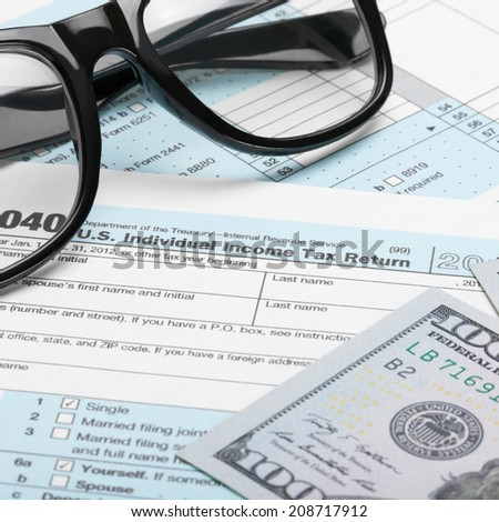 Tax Form 1040 with dollars and glasses - 1 to 1 ratio - stock photo