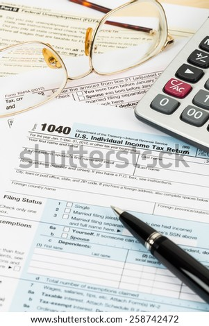 Tax form with glasses, pen, and calculator - stock photo