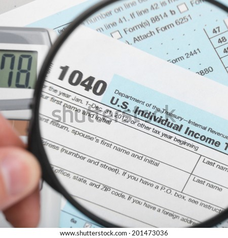 Tax Form 1040 with magnifying glass - 1 to 1 ratio - stock photo