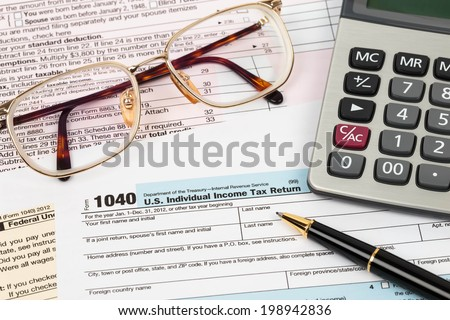 Tax form with pen, calculator, and glasses taxation concept - stock photo