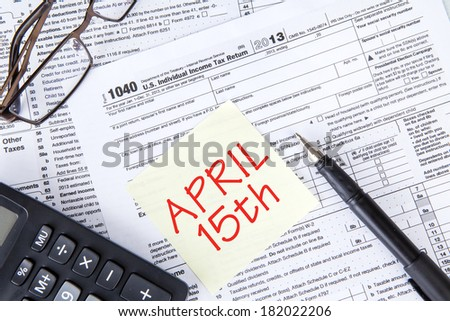 Tax form with pen, calculator, sticky note and eyeglasses - stock photo