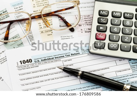 Tax form with pen, glasses, and calculator taxation concept