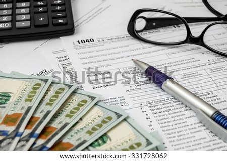 Tax form with pen, glasses, calculator and dollars
