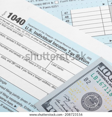 Tax Form 1040 with two 100 dollars banknotes - 1 to 1 ratio - stock photo