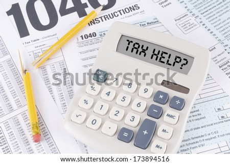 Tax Forms and Broken Pencil with a Calculator that spells out TAX HELP? in its display - stock photo