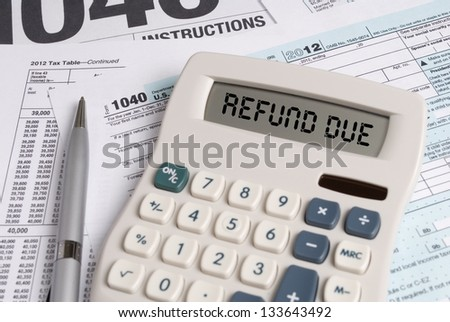 Tax Forms with Calculator that spells out REFUND DUE - stock photo