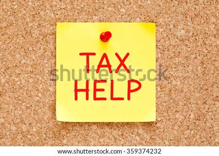 Tax Help written on yellow sticky note pinned with red push pin on cork board.