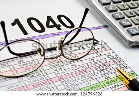 Tax papers with pen, calculator and glasses.