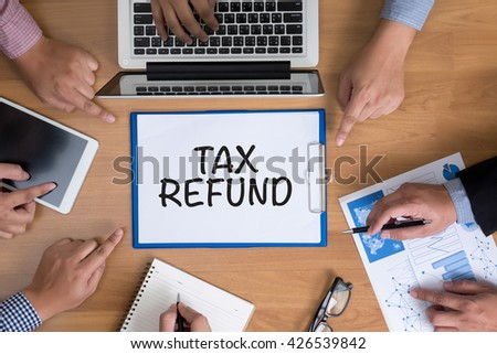 TAX REFUND Business team hands at work with financial reports and a laptop, top view - stock photo