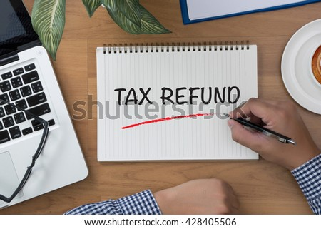TAX REFUND man hand notebook and other office equipment such as computer keyboard - stock photo