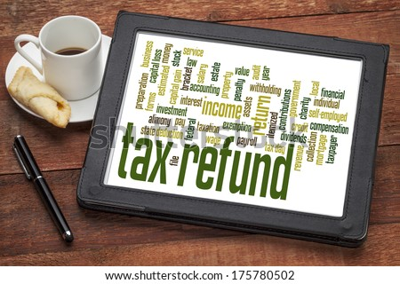 tax refund word cloud on a digital tablet with a cup of coffee - stock photo