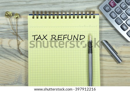 tax refund writing in notebook. pen and calculator wooden desk. business concept - stock photo