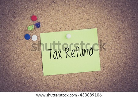 Tax Refund written on sticky note pinned on pinboard - stock photo