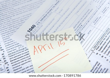 Tax reminder concept with a sticky note of april 15 and a tax form - stock photo