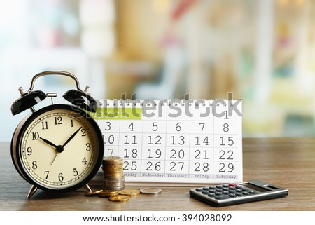 Tax time and alarm clock with coins, calculator and calendar - stock photo