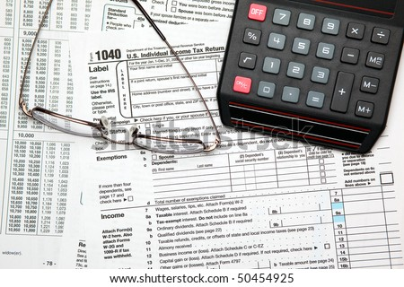 Tax time - Closeup of U.S. 1040 tax return with calculator and glasses - stock photo