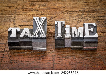 tax time - financial concept - words in mixed vintage metal type printing blocks over grunge wood - stock photo